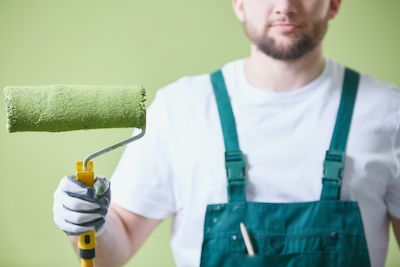 Man holding green paint roller preapred to paint the room